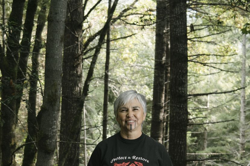 Margo Robbins, a Yurok Tribe member, stands in the forest.