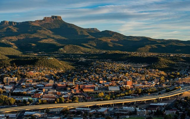 A town with an elevated highway passing through and a rocky peak in the distance.