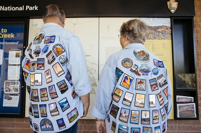 A couple wears shirts covered in patches from national parks.