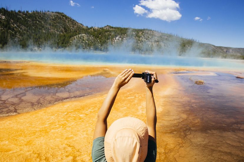 A tourist takes a photo of the Grand Prismatic Spring in Yellowstone National Park.