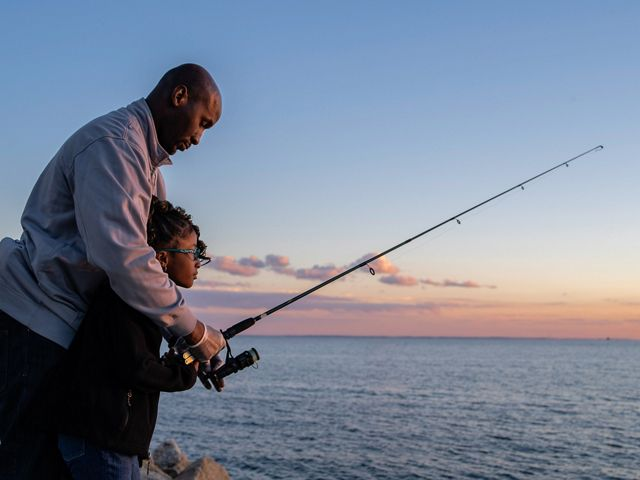 A father stands behind his daughter and helps her work a fishing pole on the coast of Bridgeport, Connecticut.