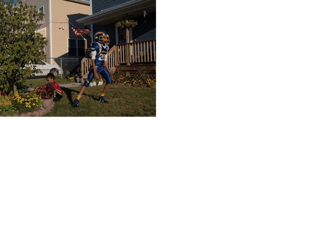 A front yard in Bridgeport, Connecticut shows a young boy near a newly planted tree and his older brother standing nearby in football gear.