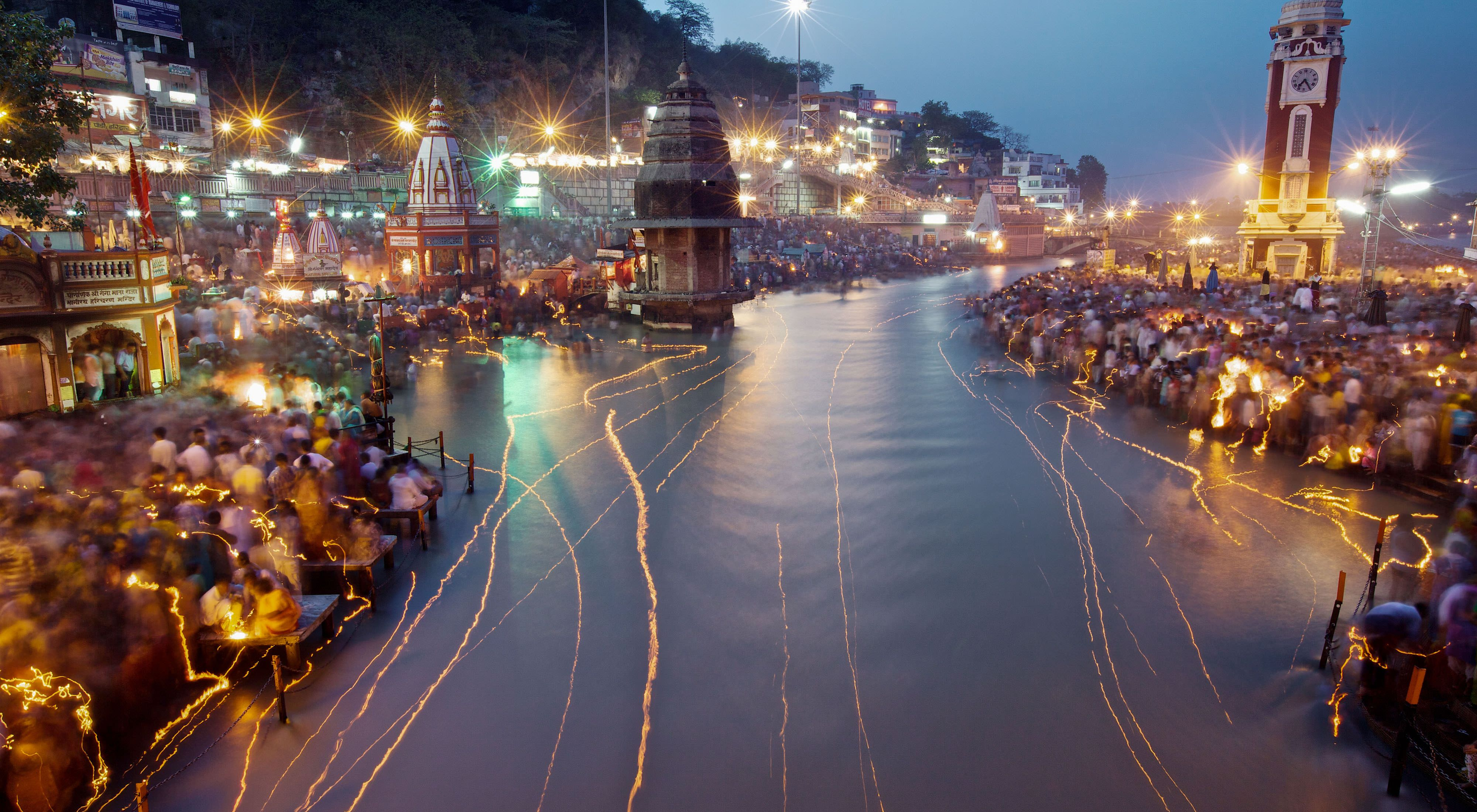 The Ganges River in India at night, reflecting the lights of buildings and passing boats