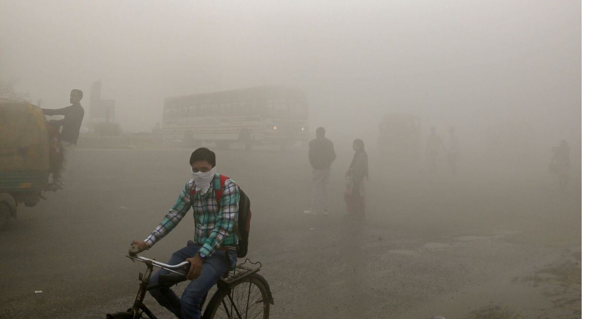 Indian commuters walk and bike through smog on the outskirts of New Delhi