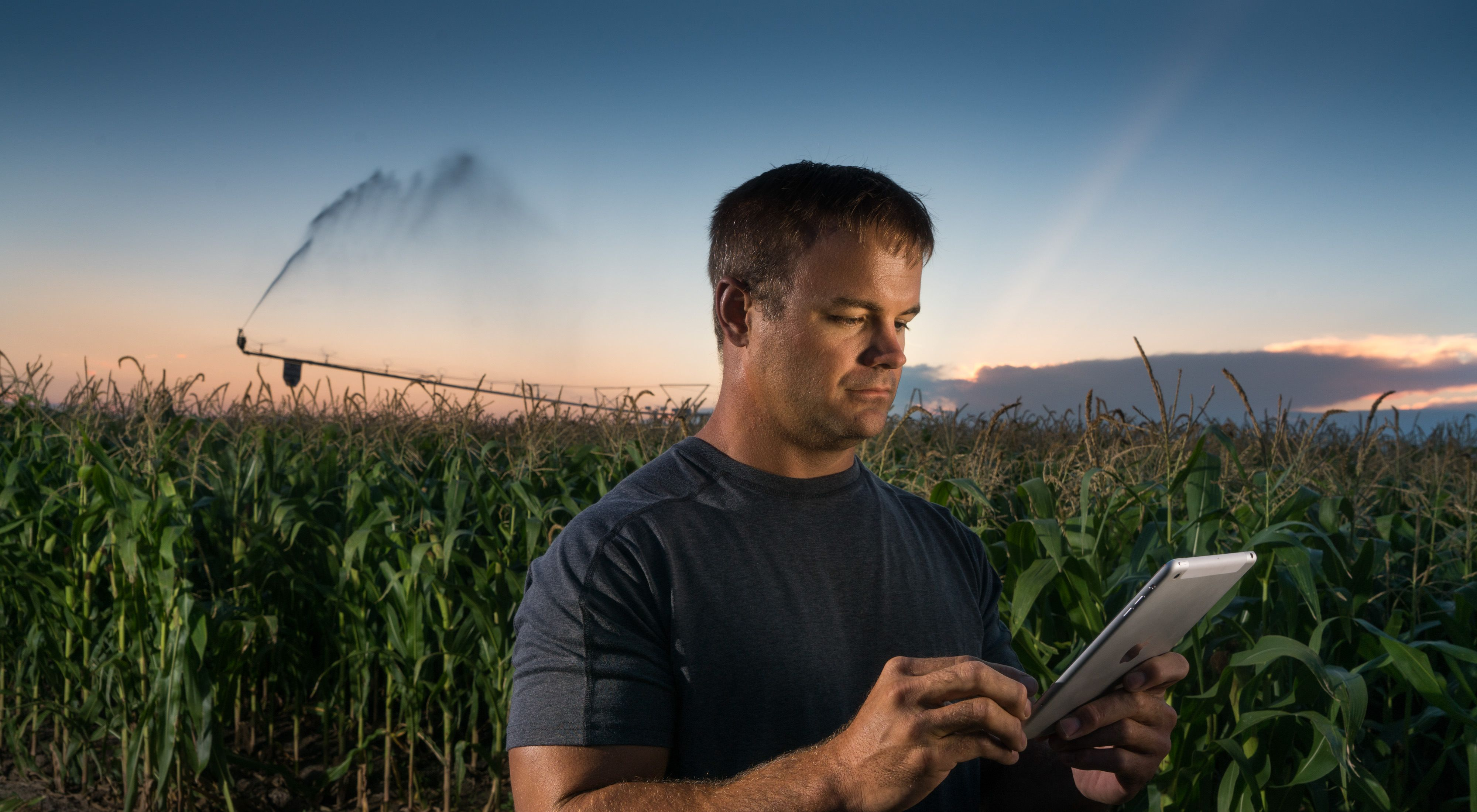 Nebraska Farmer Mike Svoboda stands in his field using a tablet to control the irrigation