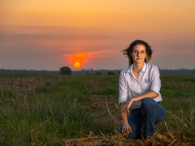 Maria Menouli kneels on her family's soy farm at sunset