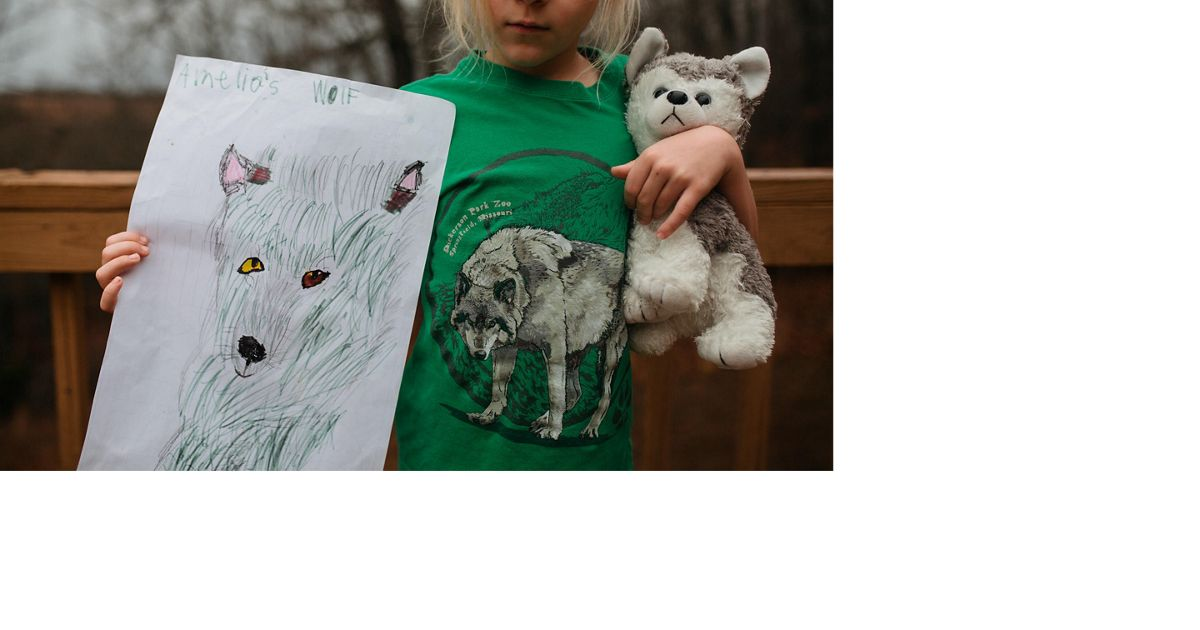 A girl holds a stuffed wolf in one arm and holds up her drawing of a wolf in the other.