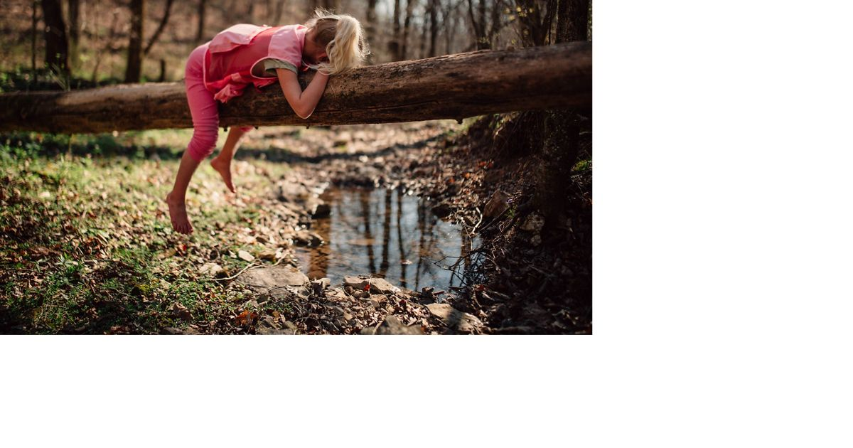 A girl lies facedown on a log over a creek.