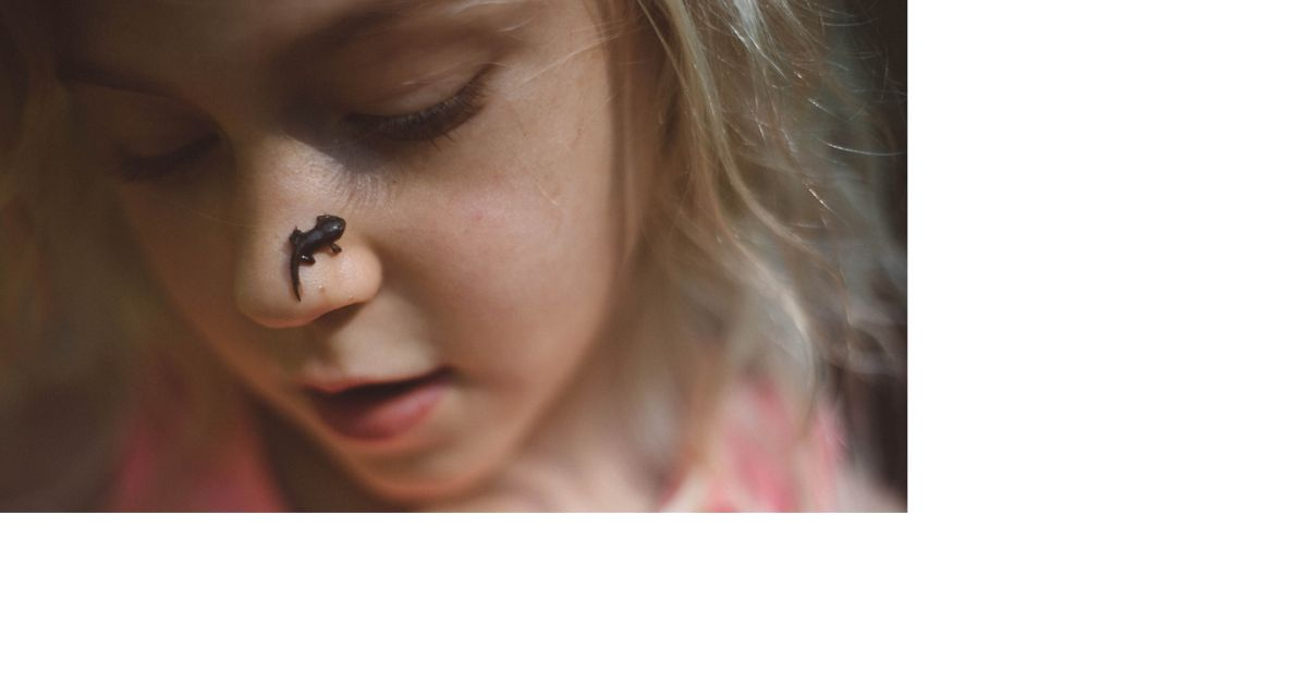 Closeup of a girl with a tadpole on her nose.