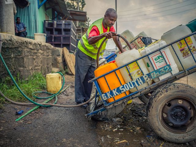 A man fills plastic containers on a cart with water