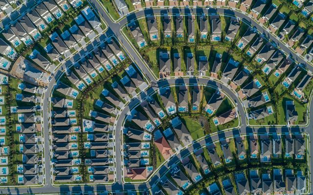 Aerial view looking directly down on an Orlando area neighborhood with densely packed houses, each with a backyard swimming pool, along curving suburban streets..
