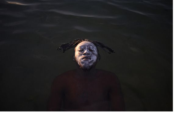 a man's face breaks the surface of a river