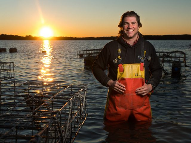 An oyster farmer stands hip deep in water near his oyster cages.