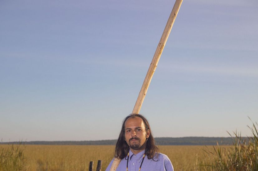 A man stands near a canoe with a long pole used to push it through the water.