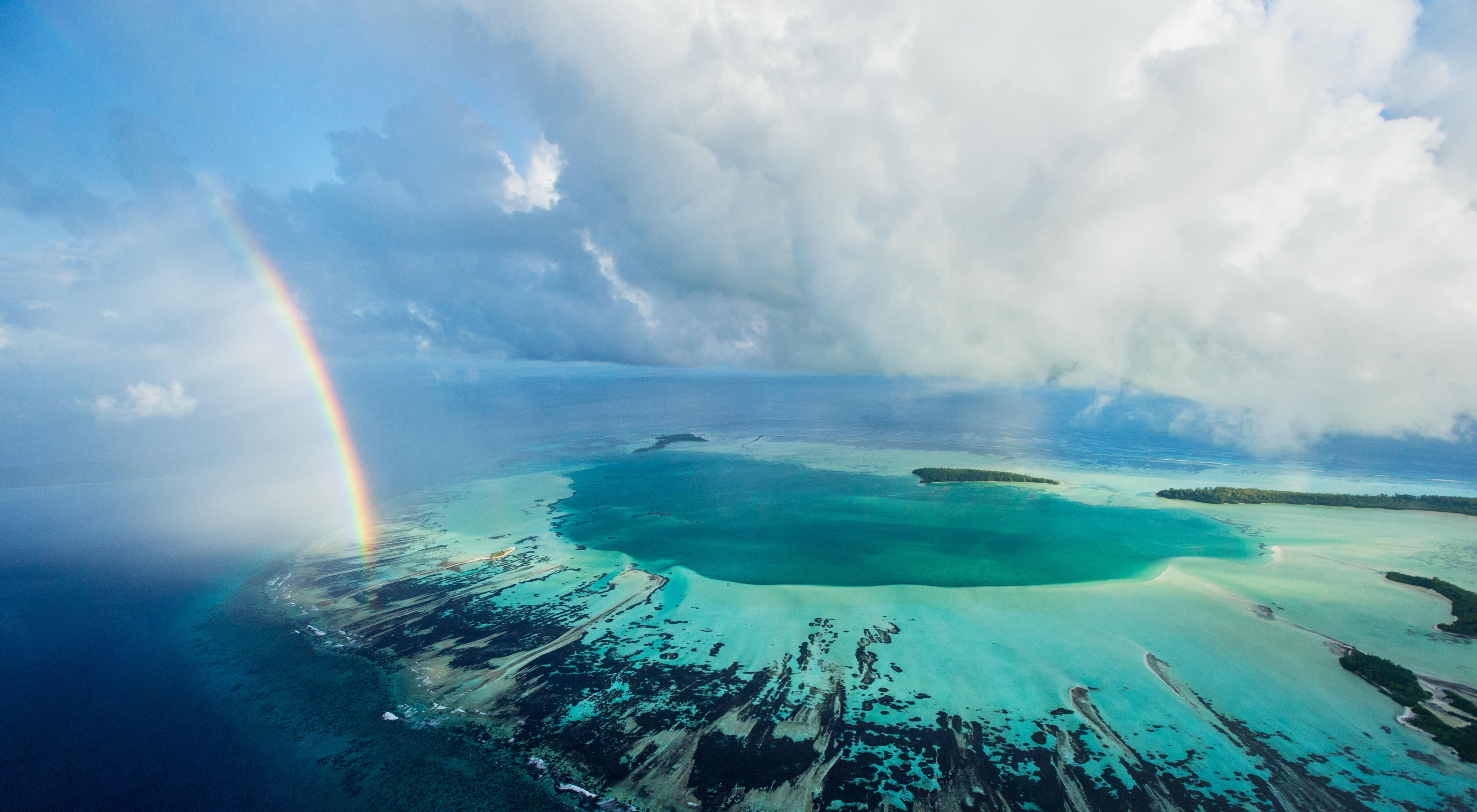 A rainbow ends at an aquamarine atoll