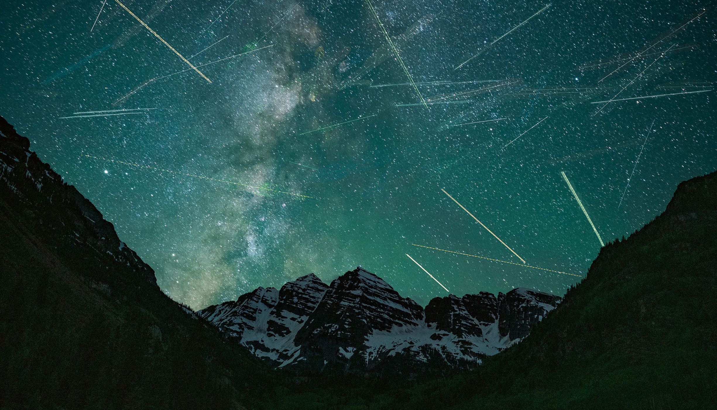blue night sky with thousands of blurred stars over dark mountains.