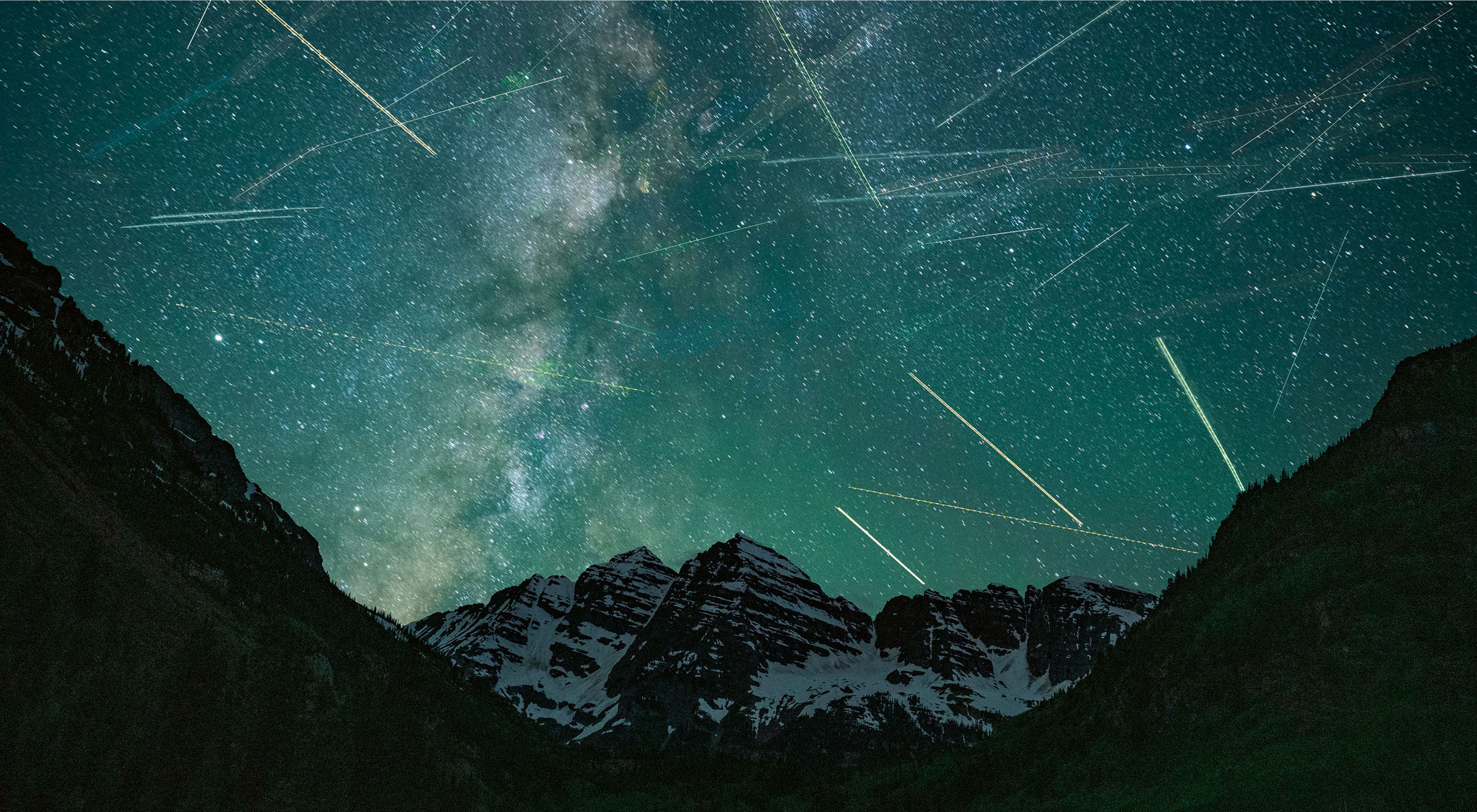 blue night sky with thousands of blurred stars over dark mountains