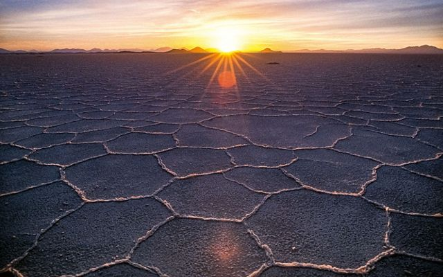 wide shot of grey ground with many hexagon shapes in the dirt leading to a sunset on a horizon