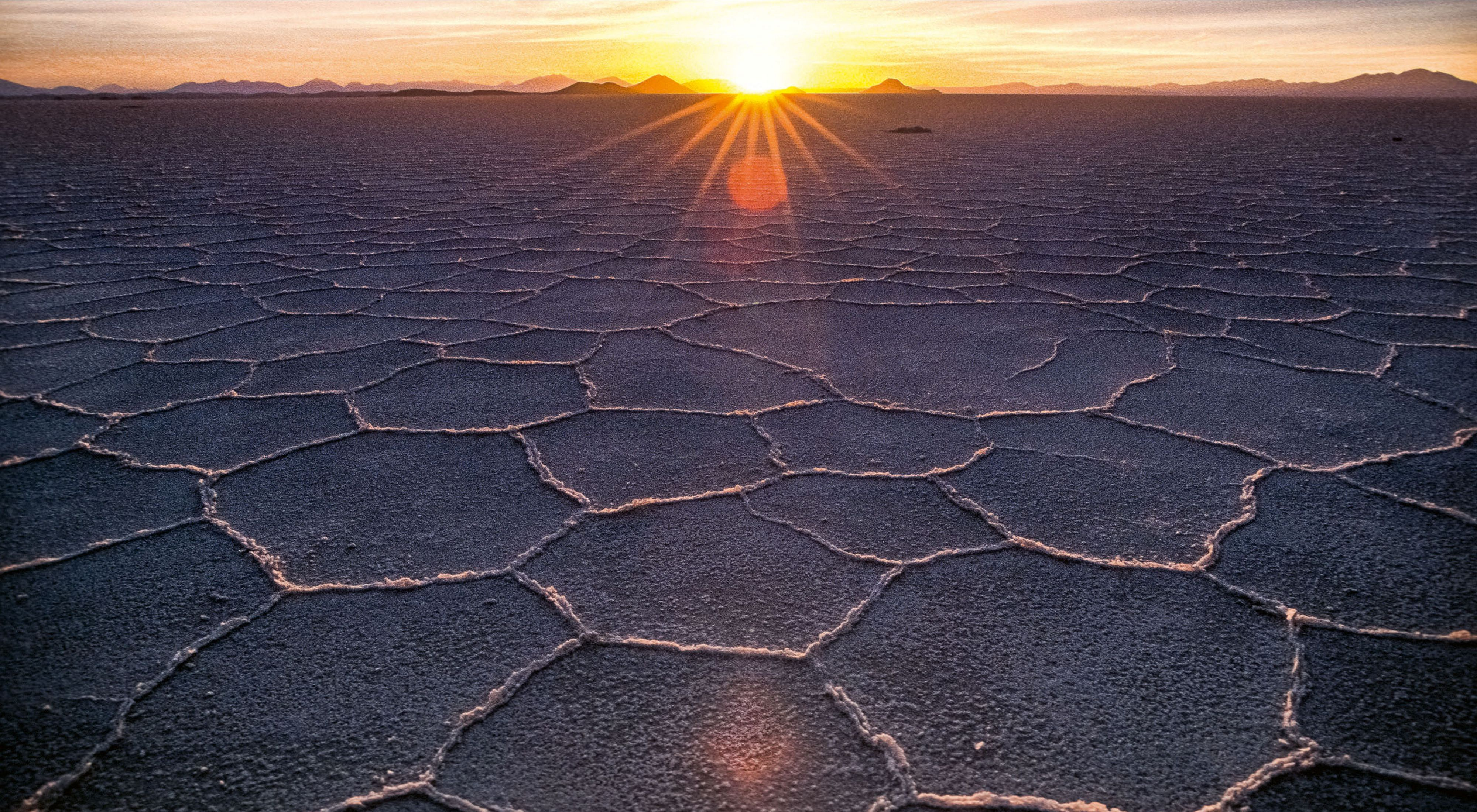 An orange sun sets over a wide plain of cracked earth.