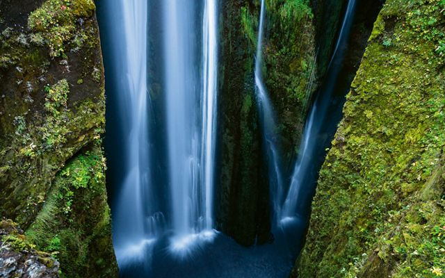blue water falls in a waterfall between two green moss-covered rock walls