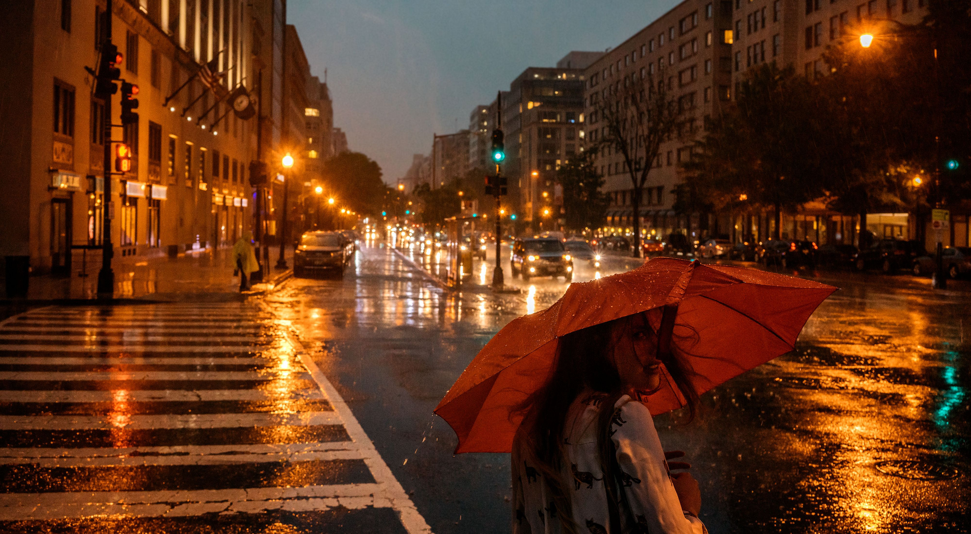 A person with a red umbrella crosses a city street at night.