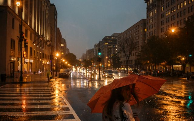 A woman holding a red umbrella waits to cross the street. Street lights and headlights are reflected on the wet pavement.