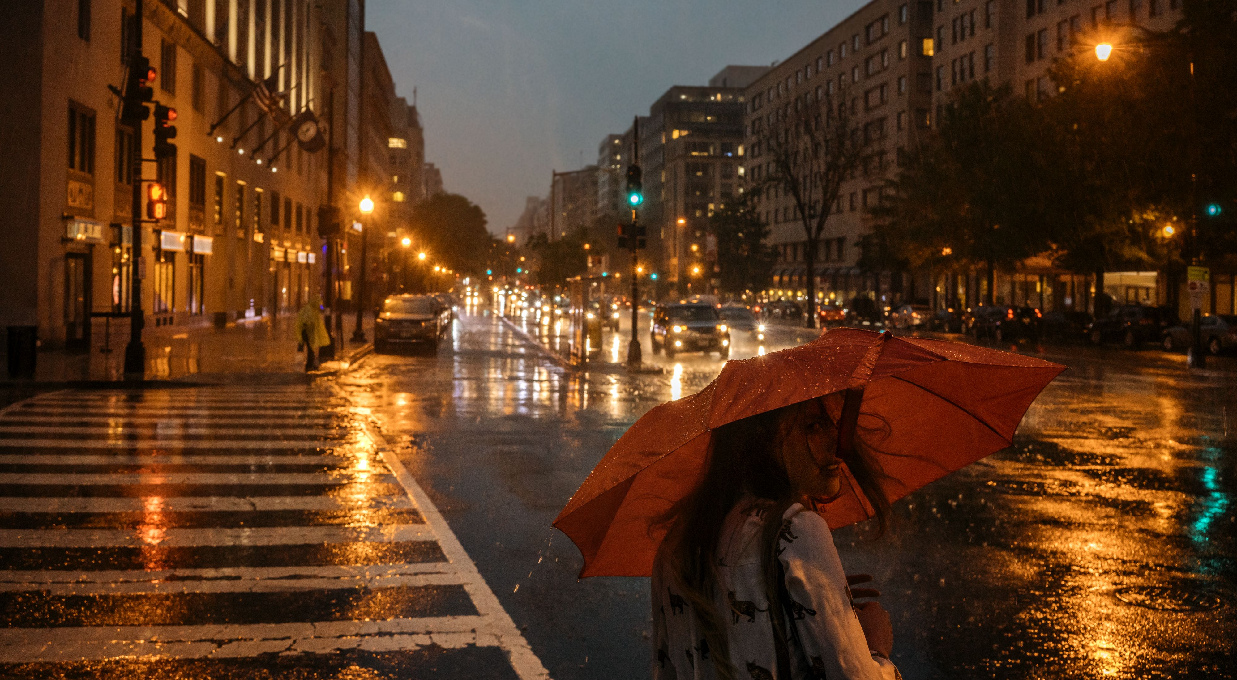 A person with a red umbrella crosses a city street at night