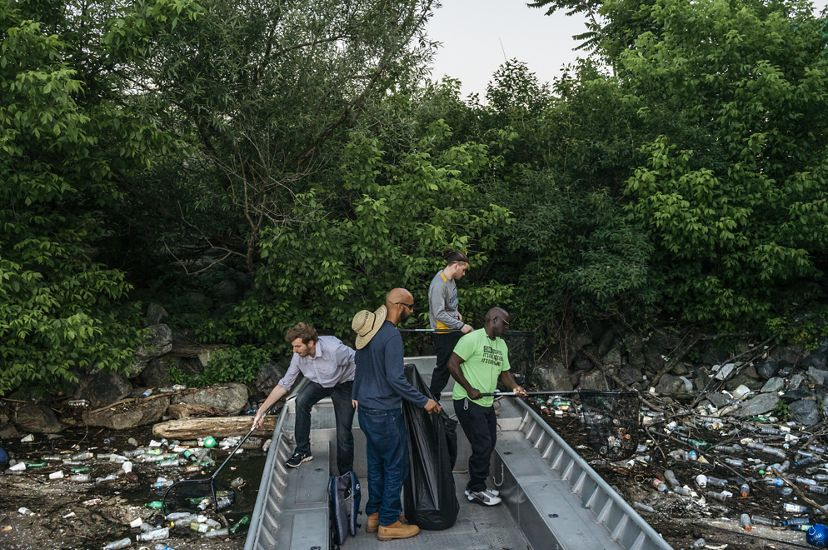 Four men scoop trash from the river's surface with nets.