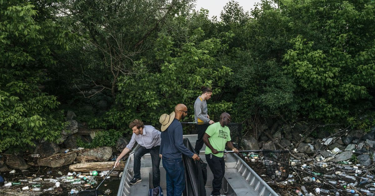 Four men scoop trash from the river's surface with nets