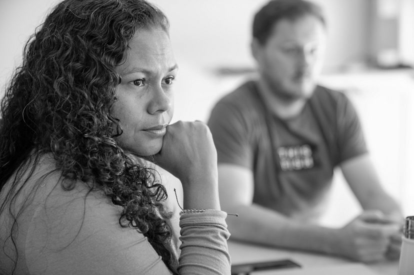 A seated woman listens intently to a Techstars presenter.