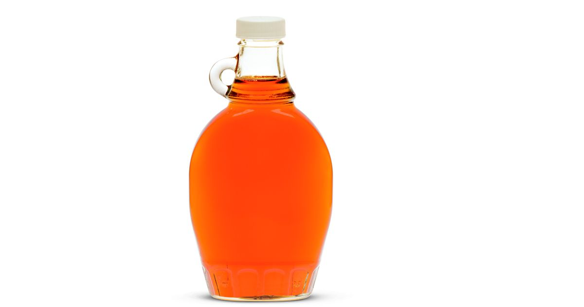 photo of a glass jug of orange-colored maple syrup, photographed on a white background