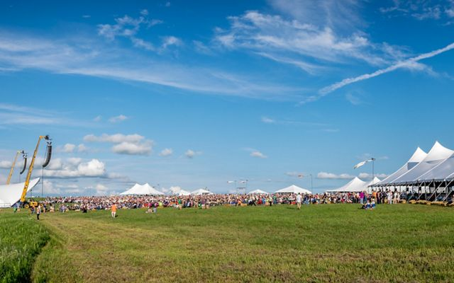 White tents on a green prairie prepare to host a symphony performance