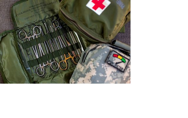 Army green medical kit is opened flat with scissors and pinchers displayed