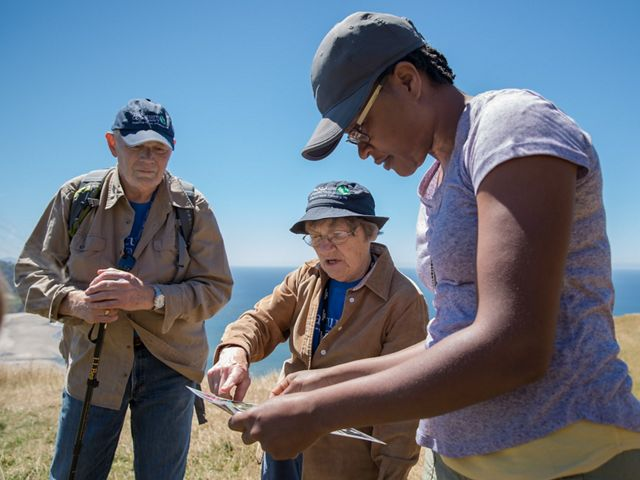 Two volunteers help a hiker at Cascade Head Preserve