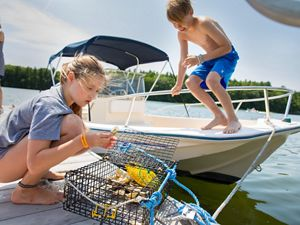 A girl on a dock examines oysters in an aquaculture cage, while a boy watches from a small motor boat moored to the dock.
