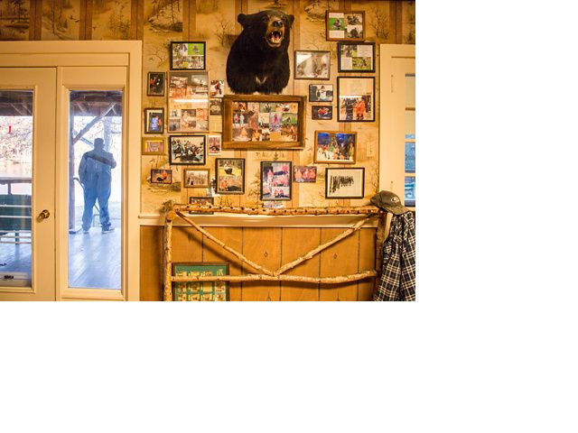 The inside of a hunting lodge with framed photos and a black bear head on the wall.