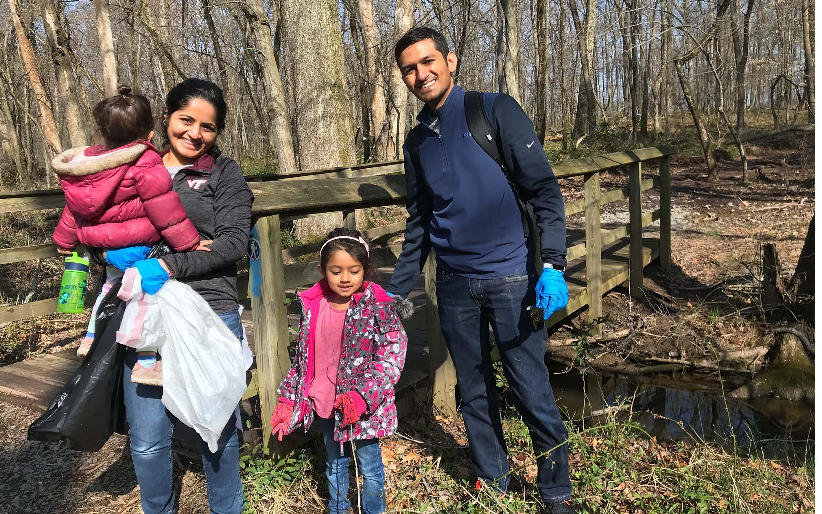 Parents with their two small children pose during an Earth Day cleanup.