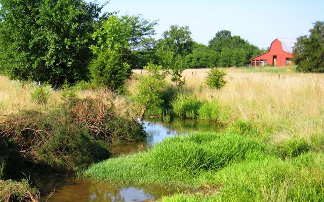 A stream winds through a field, away from a small red barn.
