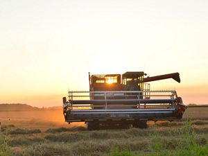 Farm combine at sunset