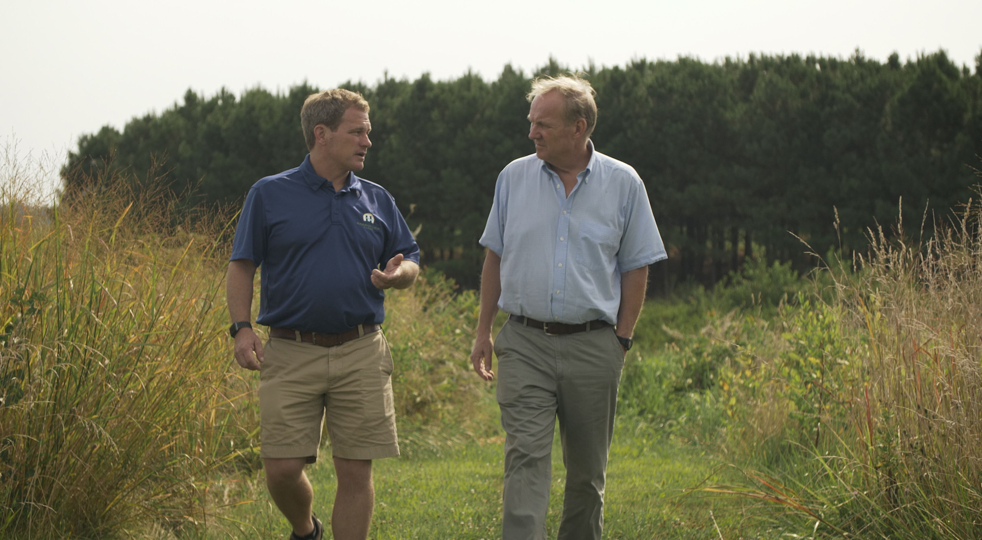 Farmer Trey Hill and landowner Joe Hickman walk through farm fields.