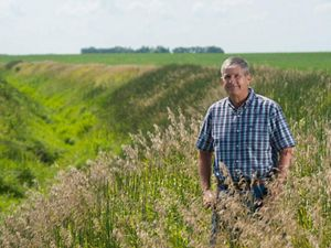 Photo of a man in a plaid shirt standing in a field of grass crops.