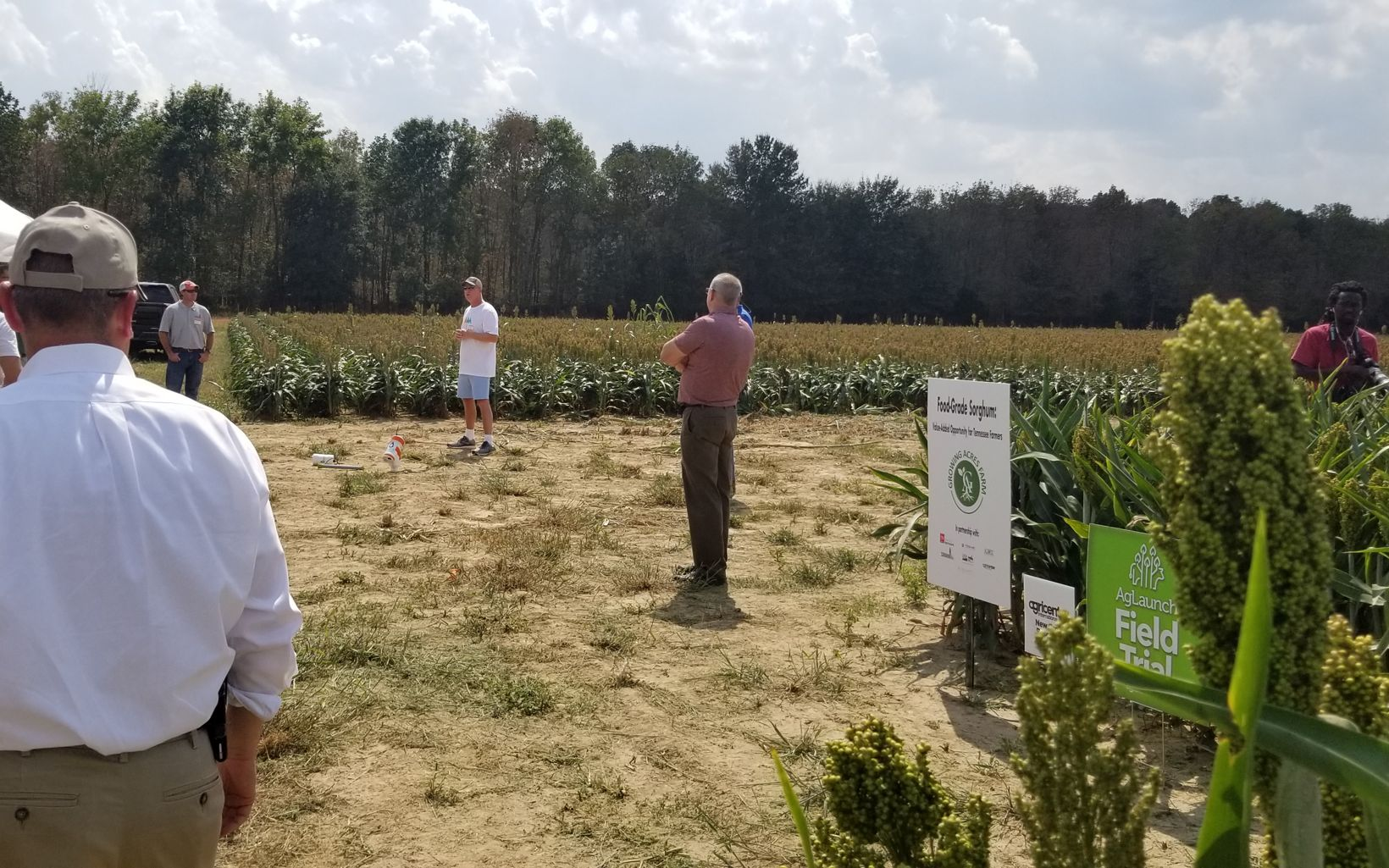 Farmers standing around a field.