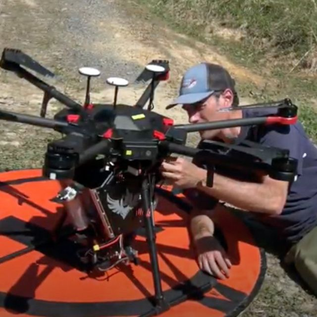 A man lays on the ground next to a large drone, readying it for deployment on a controlled burn. The drone is sitting on a round orange landing pad.