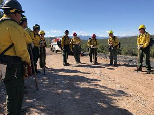 Several people in yellow prescribed fire gear and hardhats discuss plans.