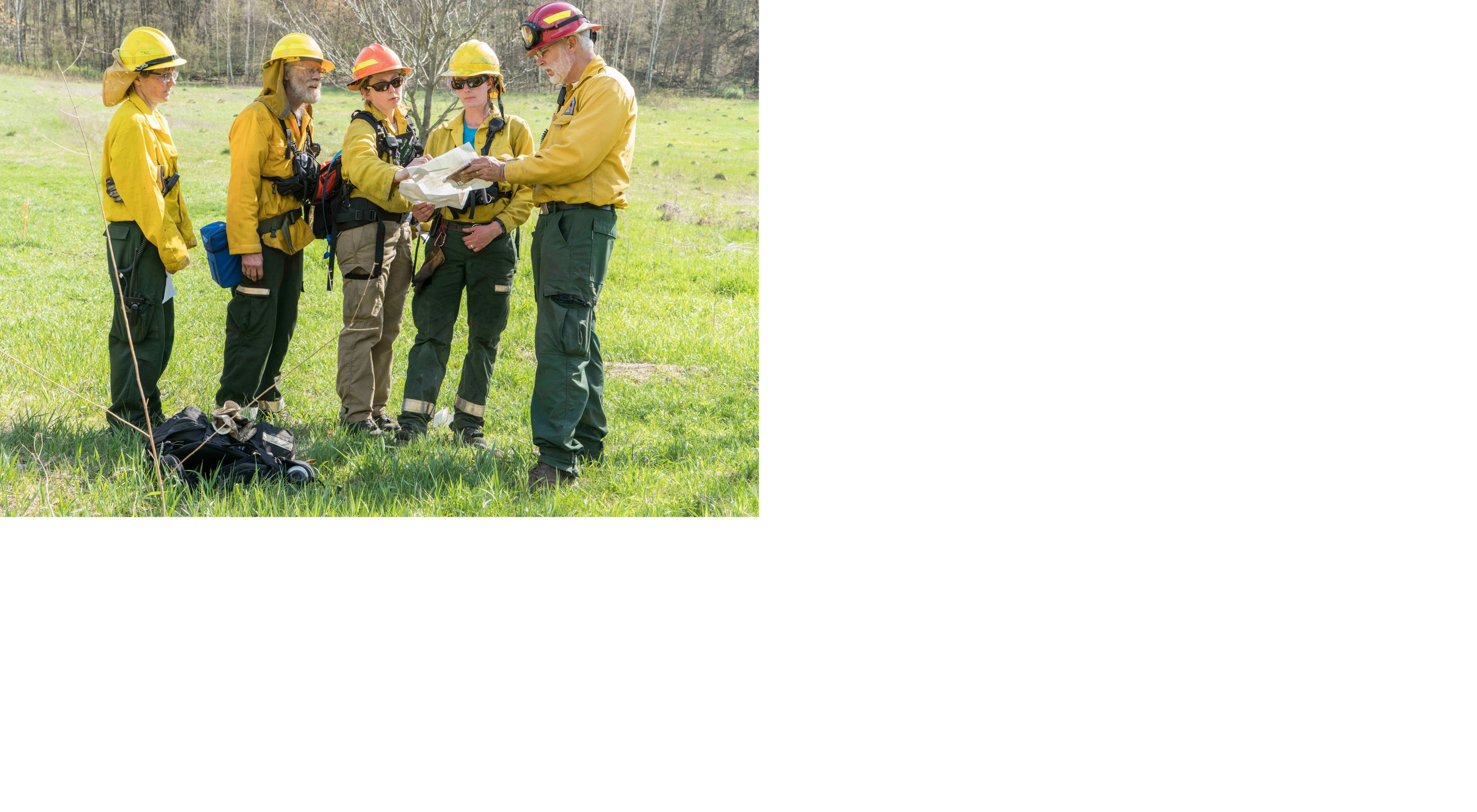Five people dressed in yellow Nomex suits, helmets, goggles and other fire gear consult maps while working on a prescribed fire in Wisconsin.
