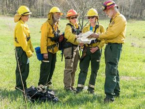 Five people dressed in fire gear look at maps