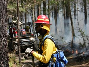 Profile view of a man resting during a controlled burn. He is wearing yellow fire gear and a red hard hat. His hands rest on the handle of a shovel. A low fire burns behind him along a fire line.