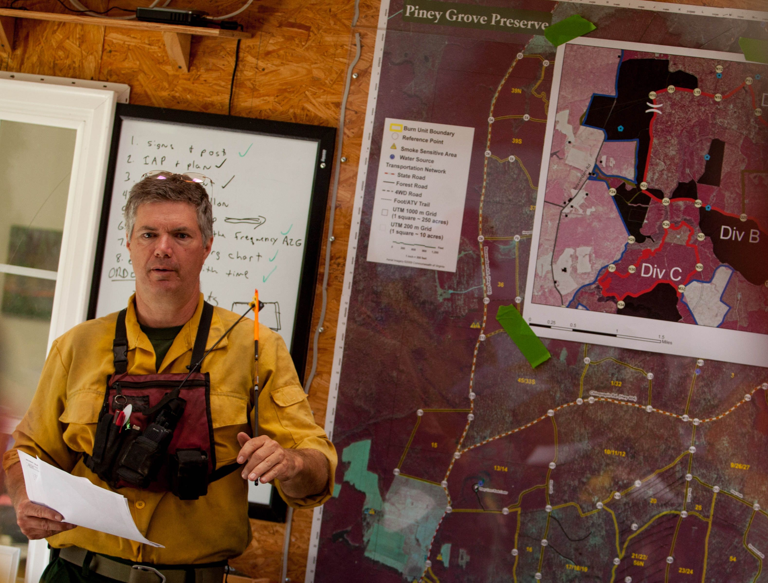 Preserve manager Bobby Clontz leads the briefing before the start of a controlled burn. A man wearing yellow fire gear stands in front of a large map showing burn areas within the preserve.