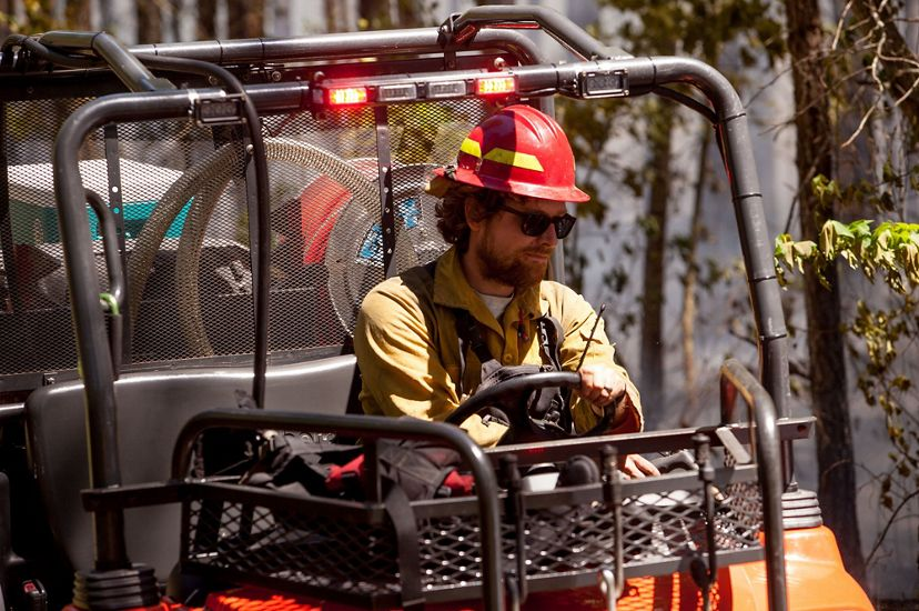 A man wearing a yellow shirt and red hard hat drives a small fire truck. The open sided all terrain vehicle contains hose and water tanks.
