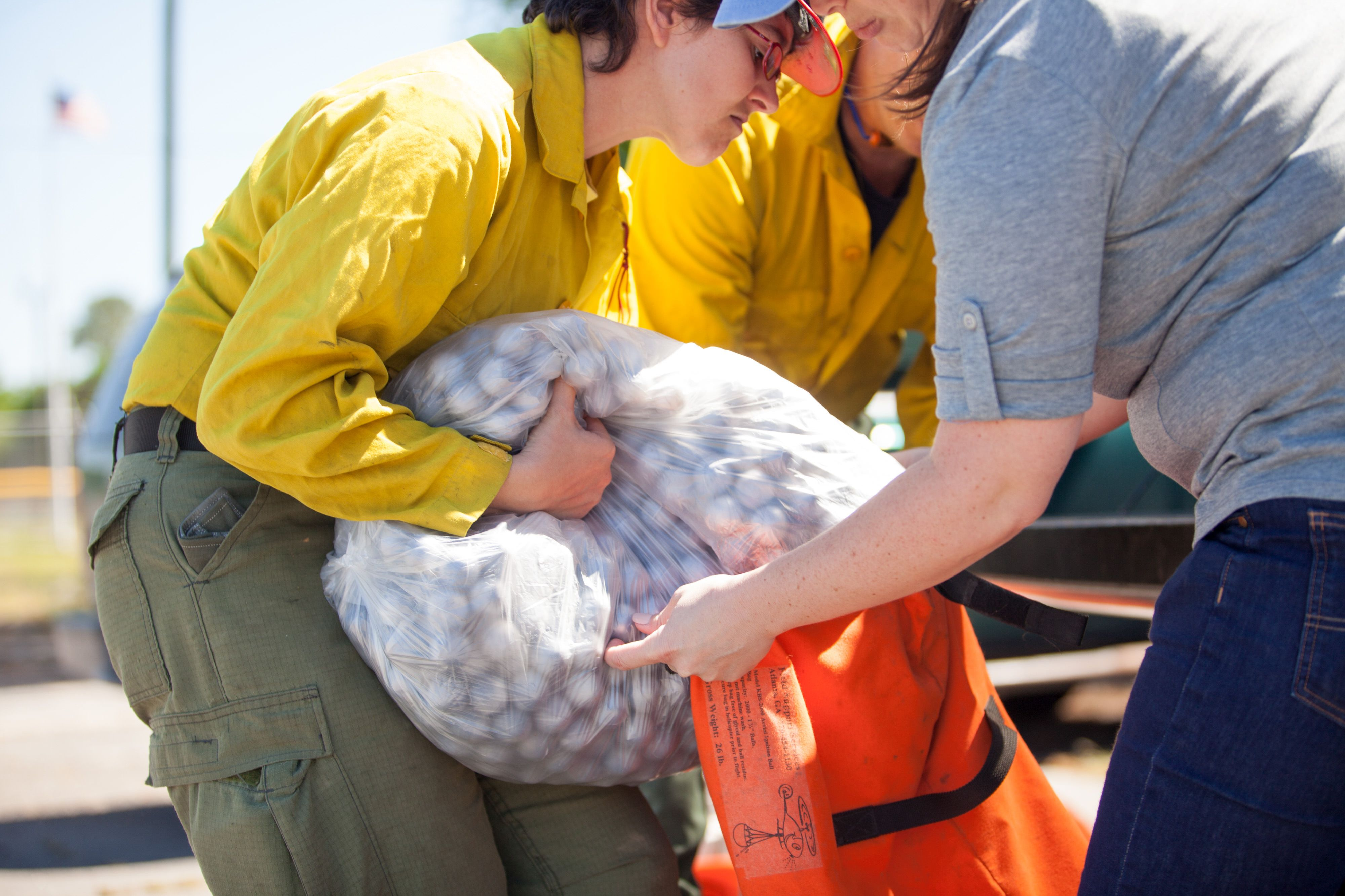 Three people huddle around an orange sack. One person holds the sack open while a second empties a clear plastic bag full of gray spheres into the sack.
